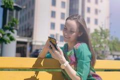 Uśmiechnięty młodej kobiety obsiadanie na żółtym ławki i używać smartphone, online komunikacja, ogólnospołeczne sieci, koresponde obraz royalty free