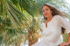 Uśmiechnięty młodej kobiety obsiadanie na drzewku palmowym Pojęcie szczęśliwy odpoczynek, li Fotografia Royalty Free