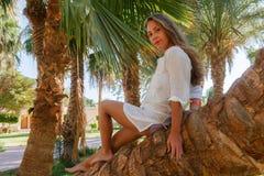 Uśmiechnięty młodej kobiety obsiadanie na drzewku palmowym Pojęcie szczęśliwy odpoczynek, li Fotografia Stock