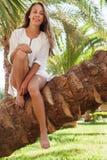 Uśmiechnięty młodej kobiety obsiadanie na drzewku palmowym Pojęcie szczęśliwy odpoczynek, li Obrazy Royalty Free