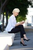 Uśmiechnięty młodej kobiety obsiadanie na zewnątrz czytelniczej wiadomości tekstowej Zdjęcia Royalty Free