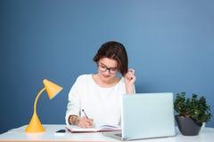 Uśmiechnięty młodej kobiety obsiadanie, writing w notatniku i obrazy stock