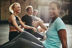 Uśmiechnięty młodej kobiety obsiadanie z przyjaciółmi na gym podłodze zdjęcie royalty free