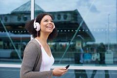 Uśmiechnięty młodej kobiety odprowadzenie z telefonem komórkowym i hełmofonami Zdjęcia Royalty Free