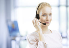 Uśmiechnięty młody żeński obsługa klienta agent z słuchawki Obrazy Royalty Free