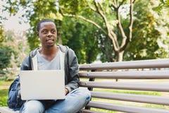Uśmiechnięty młody afroamerykański uczeń z laptopem outdoors obrazy royalty free
