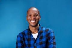 Uśmiechnięty młody afrykański mężczyzna ono uśmiecha się przeciw błękit ścianie Obraz Royalty Free