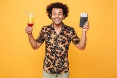 Uśmiechnięty młody afrykański mężczyzna pije koktajl i trzyma bilety Fotografia Royalty Free