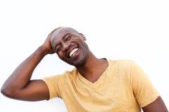 Uśmiechnięty młody afrykański mężczyzna przeciw białemu tłu obrazy stock