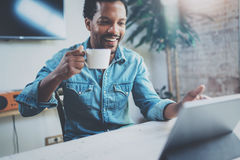Uśmiechnięty młody Afrykański mężczyzna robi wideo rozmowie przez cyfrowej pastylki z partnerami podczas gdy pijący czarną kawę w obrazy royalty free
