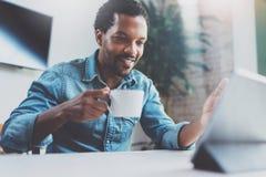 Uśmiechnięty młody Afrykański mężczyzna robi wideo rozmowie przez cyfrowej pastylki z rodziną podczas gdy pijący czarną kawę w po obraz stock