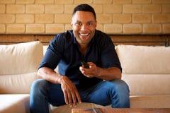Uśmiechnięty młody amerykanina afrykańskiego pochodzenia mężczyzna obsiadanie na kanapie tv i dopatrywaniu Obraz Stock