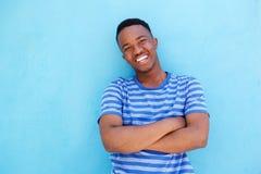 Uśmiechnięty młody amerykanina afrykańskiego pochodzenia mężczyzna opiera przeciw błękit ścianie Zdjęcia Royalty Free