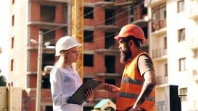 Uśmiechnięty młody architekt lub inżynieria budowniczy w ciężkim kapeluszu z falcówką w ona oddajemy grupy budowniczowie przy zbiory wideo