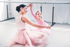 uśmiechnięty młody baletniczy nauczyciel i mały uczeń w różowym spódniczka baletnicy omijamy szkolenie wpólnie obrazy royalty free