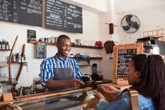 Uśmiechnięty młody barista wręcza kawę cukierniany klient Zdjęcia Royalty Free