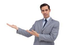 Uśmiechnięty młody biznesmen daje prezentaci z jego rękom Zdjęcie Royalty Free