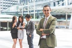 Uśmiechnięty młody biznesmen patrzeje w kamerę z jego rękami krzyżować i współczłonka drużynego tło w miastowym Nowożytna bizneso zdjęcie stock