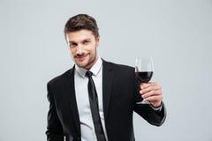 Uśmiechnięty młody biznesmen trzyma szkło czerwone wino Zdjęcie Stock