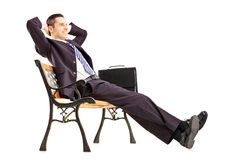 Uśmiechnięty młody biznesmena obsiadanie na relaksować i ławce Fotografia Stock