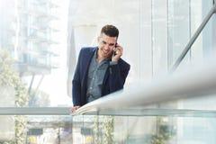 Uśmiechnięty młody biznesowego mężczyzna słuchanie z telefonem komórkowym Obraz Royalty Free