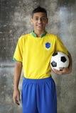Uśmiechnięty Młody Brazylijski gracz piłki nożnej w Jednolitym mienie futbolu zdjęcie stock