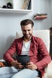 Uśmiechnięty młody brodaty mężczyzna używa pastylka komputer Obrazy Royalty Free