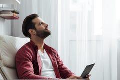 Uśmiechnięty młody brodaty mężczyzna używa pastylka komputer Zdjęcia Royalty Free