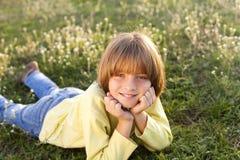 Uśmiechnięty młody chłopiec lying on the beach na trawie Obraz Royalty Free