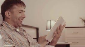 Uśmiechnięty młody człowiek śmia się przy opowieścią czyta zbiory