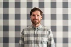 Uśmiechnięty młody człowiek jest ubranym w kratkę koszula dopasowywa jego tapetę Obraz Stock