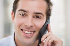Uśmiechnięty młody człowiek na telefonie komórkowym zdjęcie royalty free