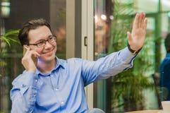 Uśmiechnięty młody człowiek opowiada na telefonie i pokazuje powitanie gest zdjęcia stock