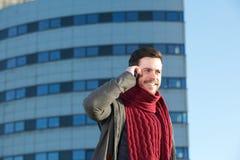 Uśmiechnięty młody człowiek opowiada na telefonie komórkowym w mieście Obraz Royalty Free