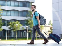 Uśmiechnięty młody człowiek podróżuje z walizką i torbą Fotografia Stock