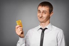 Uśmiechnięty młody człowiek trzyma kredytową kartę Zdjęcie Royalty Free