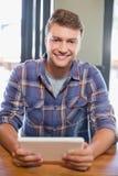 Uśmiechnięty młody człowiek używa pastylka komputer Obraz Royalty Free