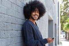 Uśmiechnięty młody człowiek używa telefon Zdjęcia Stock