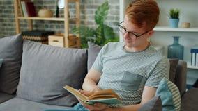 Uśmiechnięty młody człowiek w okularach czytający książkę siedzący na kanapie w mieszkaniu zdjęcie wideo