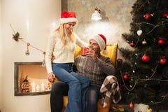 Uśmiechnięty młody człowiek w Santa ` s kapeluszowej daje teraźniejszości jego ukochany w Zdjęcia Stock