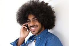 Uśmiechnięty młody człowiek z afro używa telefonem komórkowym Obraz Royalty Free