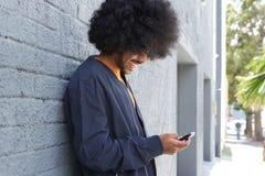 Uśmiechnięty młody człowiek z afro używa telefonem komórkowym Obrazy Royalty Free