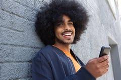 Uśmiechnięty młody człowiek z afro używa telefonem komórkowym Zdjęcie Stock