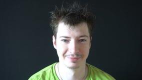 Uśmiechnięty młody człowiek z kudłacącym włosy na czarnym tle zbiory wideo