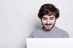 Uśmiechnięty młody człowiek z modną brodą i fryzura robi wideo wezwaniu z przyjaciółmi jest opowiadać z przyjaciółmi szczęśliwy i zdjęcia royalty free