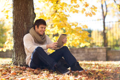 Uśmiechnięty młody człowiek z pastylka komputerem osobistym w jesień parku Obrazy Stock
