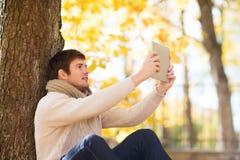 Uśmiechnięty młody człowiek z pastylka komputerem osobistym w jesień parku Fotografia Stock