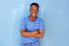 Uśmiechnięty młody czarny facet opiera przeciw błękit ścianie Obrazy Stock