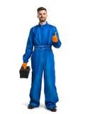 Uśmiechnięty młody mechanik w kotłowym kostiumu daje kciukowi up przeciw Zdjęcie Royalty Free