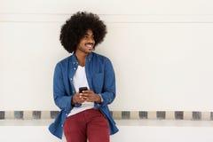 Uśmiechnięty młody murzyn używa telefon komórkowego Obrazy Royalty Free